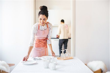 Young housewife wearing apron laying dining table Stock Photo - Premium Royalty-Free, Code: 649-08565977