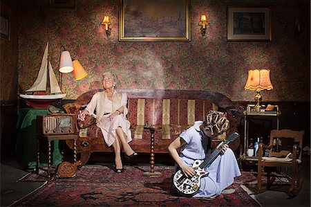 Girl playing guitar at grandmother's Stock Photo - Premium Royalty-Free, Code: 649-08560617