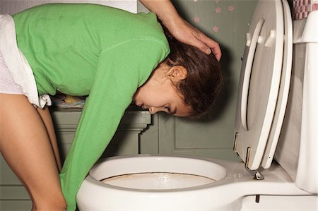 Girl being sick in toilet Stock Photo - Premium Royalty-Free, Code: 649-08562872