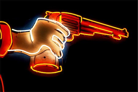 Neon sign of hand holding gun Stock Photo - Premium Royalty-Free, Code: 649-08563901