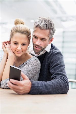 Couple sitting together at table, looking at smartphone Stock Photo - Premium Royalty-Free, Code: 649-08576448