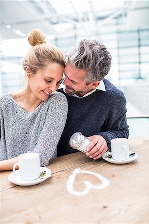 Couple sitting together, drinking coffee, heart shape made from sugar on table in front of them Stock Photo - Premium Royalty-Free, Code: 649-08576450
