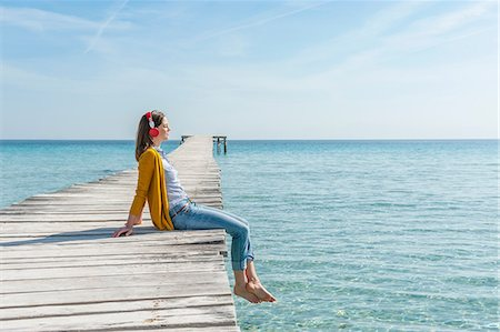 Mid adult woman sitting on edge of pier, wearing headphones Stock Photo - Premium Royalty-Free, Code: 649-08576480
