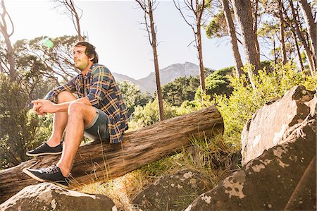 friluftsliv - Male hiker sitting on fallen tree in forest, Deer Park, Cape Town, South Africa Stock Photo - Premium Royalty-Free, Code: 649-08576584