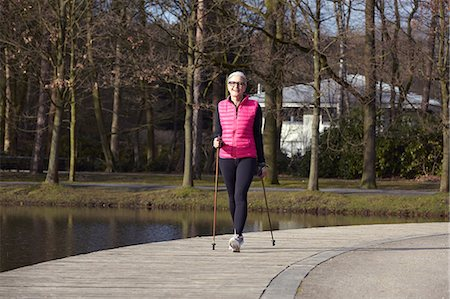 Full length front view of woman nordic walking by pond Stock Photo - Premium Royalty-Free, Code: 649-08576922