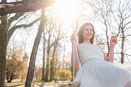 Woman wearing chiffon dress swinging on tree swing smiling Stock Photo - Premium Royalty-Free, Code: 649-08577025