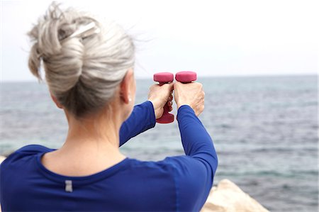 fitness   mature woman - Mature woman beside sea, exercising with hand weights, rear view Stock Photo - Premium Royalty-Free, Code: 649-08577020