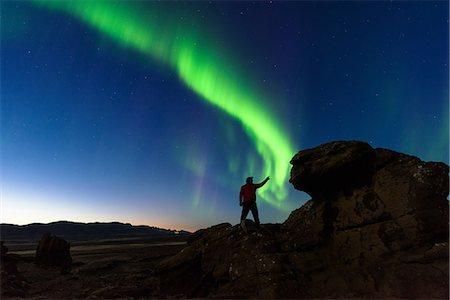 person - Man standing on rocks, watching Northern Lights, Krysuvik, Iceland Stock Photo - Premium Royalty-Free, Code: 649-08577485