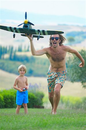father son shirtless - Father and son flying remote control plane, outdoors Stock Photo - Premium Royalty-Free, Code: 649-08577497