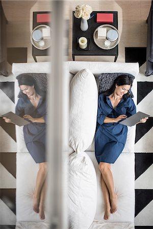 rich lifestyle - Overhead view of woman lying on hotel room sofa using digital tablet, Dubai, United Arab Emirates Stock Photo - Premium Royalty-Free, Code: 649-08577529