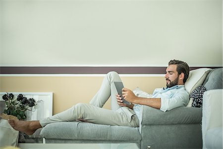 side - Young man reclining on hotel room chaise longue using digital tablet, Dubai, United Arab Emirates Stock Photo - Premium Royalty-Free, Code: 649-08577538