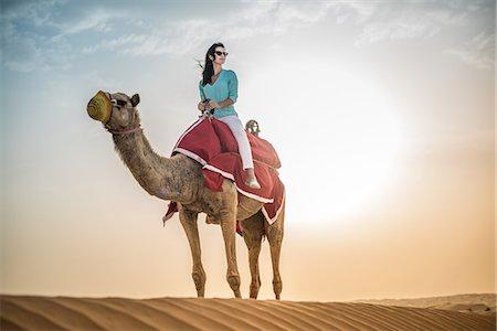Female tourist riding camel in desert, Dubai, United Arab Emirates Stock Photo - Premium Royalty-Free, Code: 649-08577598