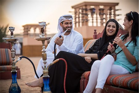 smoke - Local couple wearing traditional clothes smoking shisha on sofa with female tourist, Dubai, United Arab Emirates Stock Photo - Premium Royalty-Free, Code: 649-08577604
