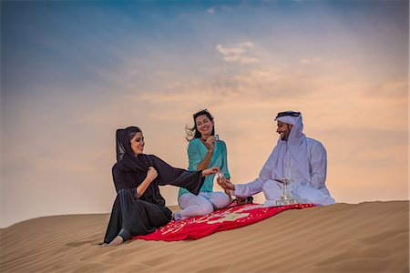 picture - Local couple wearing traditional clothes picnicing on desert dune with female tourist, Dubai, United Arab Emirates Stock Photo - Premium Royalty-Free, Code: 649-08577606