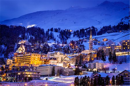 Village beneath mountain on snow covered landscape illuminated in the evening, Sankt Moritz, Switzerland Stock Photo - Premium Royalty-Free, Code: 649-08577930