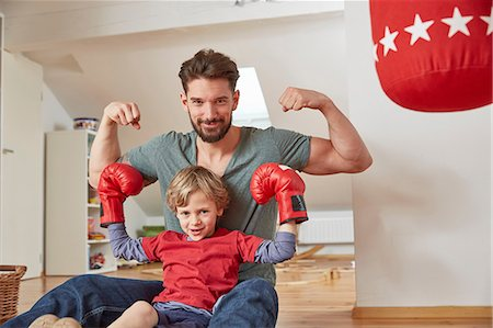 Boy wearing boxing with father, flexing muscles looking at camera Stock Photo - Premium Royalty-Free, Code: 649-08578061