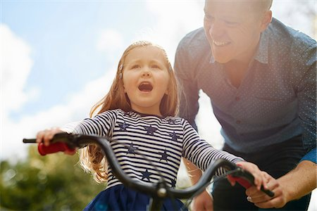 Father teaching daughter to ride bicycle Stock Photo - Premium Royalty-Free, Code: 649-08578148