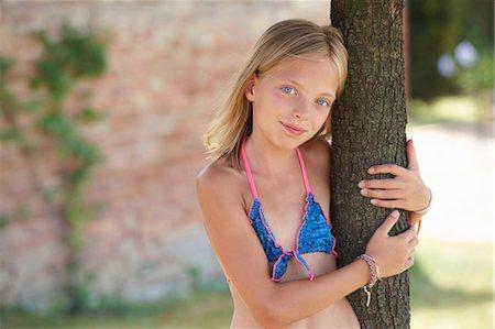 Portrait of girl wearing bikini top leaning against tree, Buonconvento, Tuscany, Italy Stock Photo - Premium Royalty-Free, Code: 649-08578166