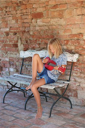 Girl sitting on bench playing ukulele, Buonconvento, Tuscany, Italy Stock Photo - Premium Royalty-Free, Code: 649-08578171