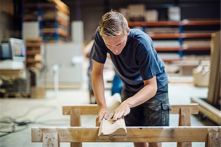 Young male carpenter sanding wood in workshop Stock Photo - Premium Royalty-Free, Code: 649-08633265