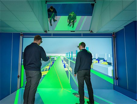 Engineers inspecting factory layout in 3D in virtual reality suite Stock Photo - Premium Royalty-Free, Code: 649-08660765