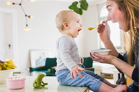Baby girl mimicking mother whilst eating  at kitchen table Stock Photo - Premium Royalty-Free, Code: 649-08661488