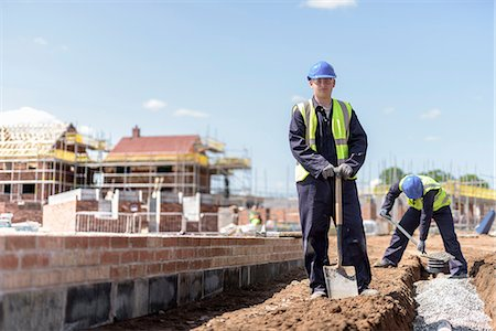 pipework - Portrait of apprentice builder laying pipework on housing building site Stock Photo - Premium Royalty-Free, Code: 649-08661674