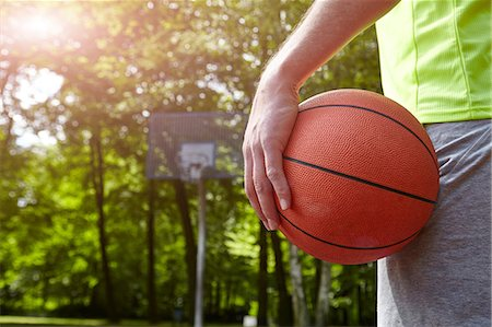 Cropped close up of young male basketball player holding ball Stock Photo - Premium Royalty-Free, Code: 649-08661718