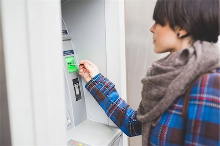 Young woman using cash machine, rear view Stock Photo - Premium Royalty-Free, Code: 649-08661793