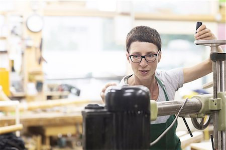 Woman in workshop using machinery Stock Photo - Premium Royalty-Free, Code: 649-08661847