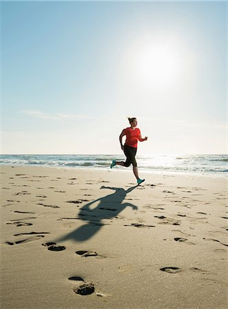 Mature woman running on a beach at sunset Stock Photo - Premium Royalty-Free, Code: 649-08702370