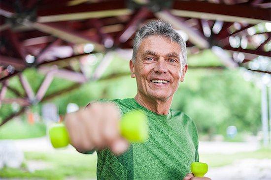 Portrait of senior man weight lifting dumbbells under bridge Stock Photo - Premium Royalty-Free, Image code: 649-08702395
