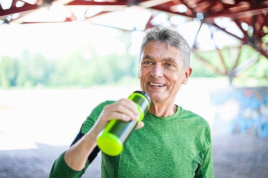Senior male runner drinking from water bottle under bridge Stock Photo - Premium Royalty-Free, Image code: 649-08702397