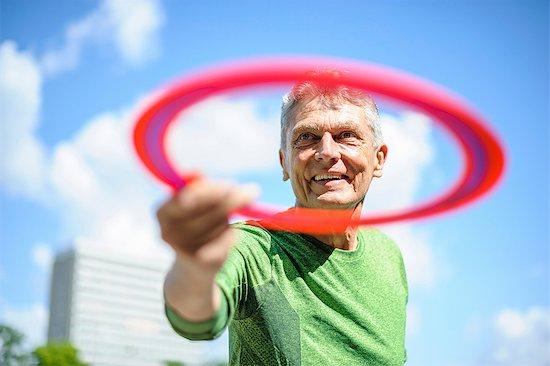 Senior man throwing flying ring against blue sky Stock Photo - Premium Royalty-Free, Image code: 649-08702393