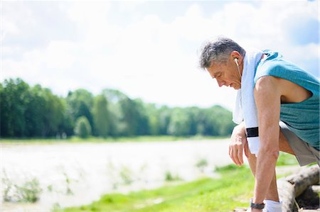 sports - Senior male runner tying trainer laces by river Stock Photo - Premium Royalty-Free, Code: 649-08702404