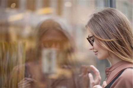 Beautiful woman gazing at shop window, Freiburg, Germany Stock Photo - Premium Royalty-Free, Code: 649-08702425