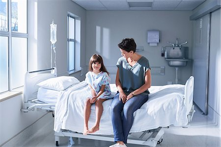 Girl patient and her mother sitting on bed in hospital children's ward Stock Photo - Premium Royalty-Free, Code: 649-08702734