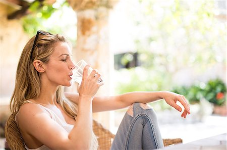 drink (non-alcohol) - Young woman relaxing on garden patio drinking water Stock Photo - Premium Royalty-Free, Code: 649-08703272