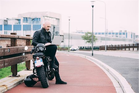 Mature male motorcyclist sitting on roadside using laptop Stock Photo - Premium Royalty-Free, Code: 649-08714748