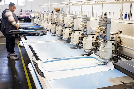 Female factory worker preparing cloth for speed stitching  programmed embroidery machine in clothing factory Stock Photo - Premium Royalty-Free, Code: 649-08714901