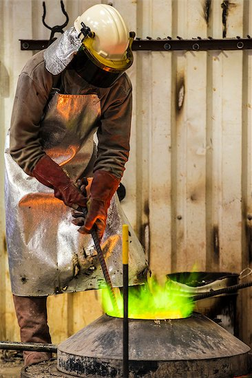 Male foundry worker working with green flamed furnace in bronze foundry Stock Photo - Premium Royalty-Free, Image code: 649-08715041