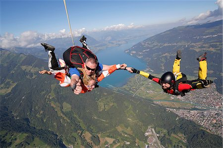 Smiling tandem sky divers holding hand with free faller, Interlaken, Berne, Switzerland Stock Photo - Premium Royalty-Free, Code: 649-08715053