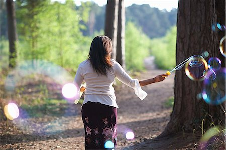 photografia - Rear view of woman in forest making bubbles with bubble wand Foto de stock - Royalty Free Premium, Número: 649-08715078