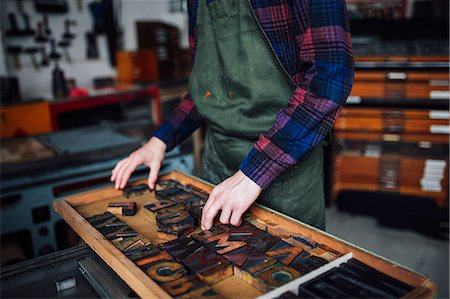 Crop of young craftsman looking through tray of wooden letterpress letters in print workshop Stock Photo - Premium Royalty-Free, Code: 649-08744912