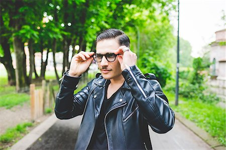 Man adjusting spectacles in park Stock Photo - Premium Royalty-Free, Code: 649-08745001