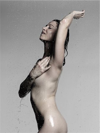 Naked mature woman showering with hand on chest and arm raised Stock Photo - Premium Royalty-Free, Code: 649-08745144