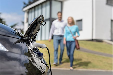 Man and woman walking towards electric car being charged Stock Photo - Premium Royalty-Free, Code: 649-08745220