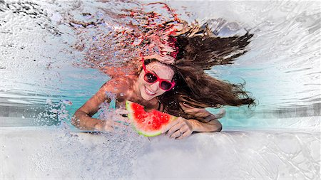 Underwater view of woman wearing sunglasses, eating slice of water melon, smiling Stock Photo - Premium Royalty-Free, Code: 649-08745494