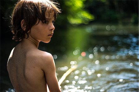Rear view of boy by water looking away over shoulder Stock Photo - Premium Royalty-Free, Code: 649-08745639