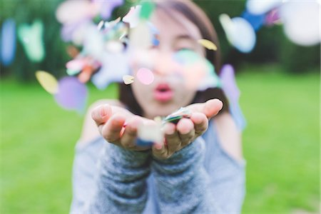 Close up of young woman in park blowing handful of confetti Stock Photo - Premium Royalty-Free, Code: 649-08824081